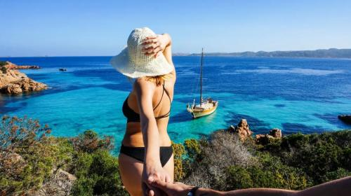 Girl and vintage sailing ship in the crystal clear sea