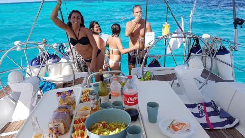 Escursionisti durante pranzo in barca a vela nel nord della Sardegna