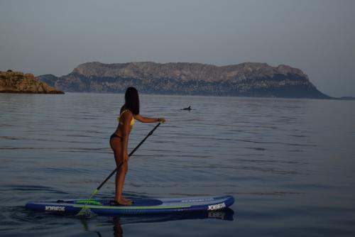 Ragazza in SUP al tramonto a Golfo Aranci
