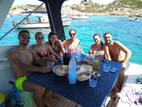 Gruppo di ragazzi a bordo di una barca a motore nell'Arcipelago di La Maddalena