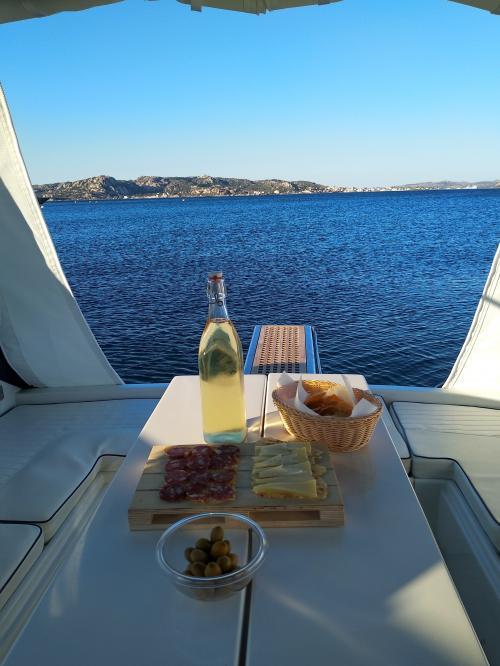 Aperitivo con bottiglia di vino bianco a bordo di una barca nell'Arcipelago di La Maddalena