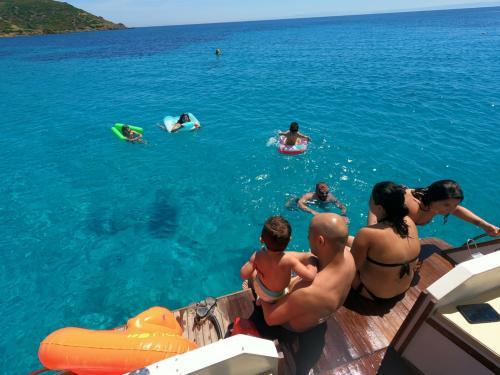 Famiglia fa il bagno nel Golfo dell'Asinara durante escursione con gozzo in legno