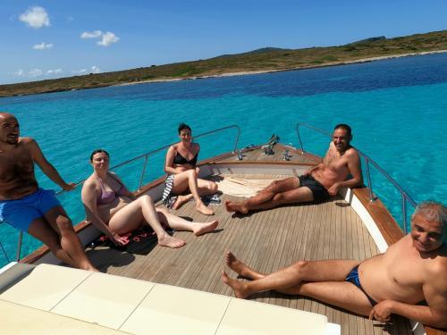 Gruppo di amici in relax a prua in un gozzo in legno nel Golfo dell'Asinara