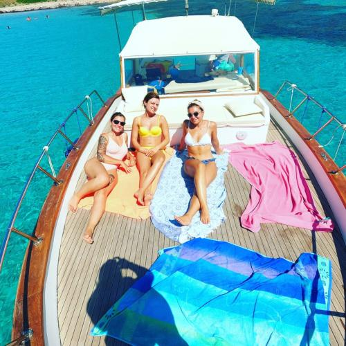 Wanderer entspannen sich während des Ausflugs in der Sonne an Bord eines hölzernen Gozzo