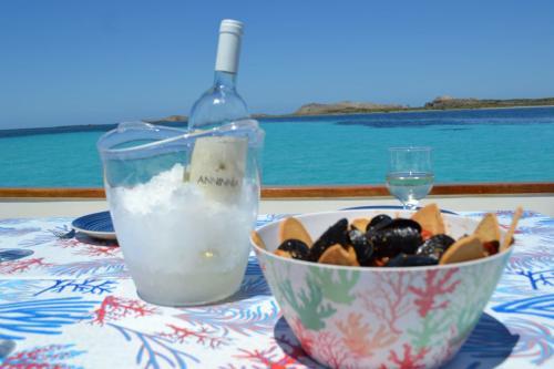 Vino bianco in ghiaccio e ciotola di cozze a bordo di un gozzo in legno nel Golfo dell'Asinara